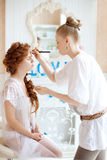 Stylist makes makeup bride on the wedding day Stock Photos