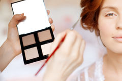 Stylist makes makeup bride on the wedding day Royalty Free Stock Photography
