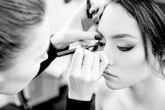 Stylist makes professional eye makeup. Beautiful model. Grayscale Stock Photography