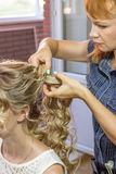 Stylist makes wedding hairstyle. Royalty Free Stock Photo