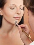 Stylist making make-up. Stylist applying make-up to young beautiful women royalty free stock photo