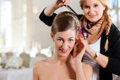 Stylist pinning up a bride's hairstyle. Before the wedding Royalty Free Stock Images