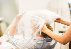 Stylist pinning up a bride's hairstyle and bridal veil before the wedding Royalty Free Stock Photography