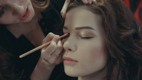 Stylist puts on the eyelids of a brunette model a dark eye shadow. stock video