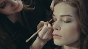 Stylist puts on the eyelids of a brunette model a dark eye shadow. stock video footage
