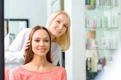 Stylist is showing hairdo to her client stock photos