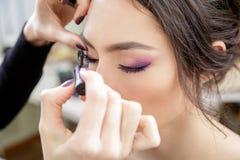 Stylist som applicerar mascara på ögonfrans av modellen Royaltyfria Bilder