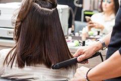 Stylist som framlänges använder järn på hår av den kvinnliga klienten royaltyfria bilder