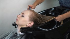 Stylist sprays hair with hose to rinse female customer`s hair at salon stock footage