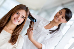 Stylist straightening hair Royalty Free Stock Images