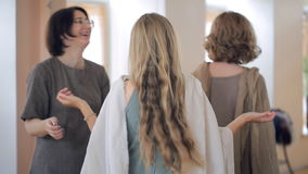 Stylist teaches women to wear shawls on group lessons. We see two ladies trying not to let scarf fell down from their shoulders in front of mirror. One student stock footage
