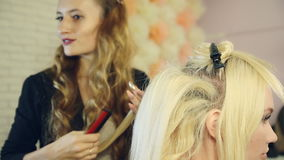 Stylist using curling iron and does curls on blonde girl hair. stock video footage