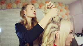 Stylist using curling iron and does curls on blonde girl hair. stock footage