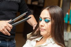 Stylist Using Flat Iron on Hair of Female Client Royalty Free Stock Image