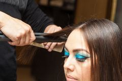 Stylist Using Flat Iron on Hair of Female Client Stock Photos