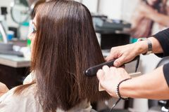Stylist Using Flat Iron on Hair of Female Client Royalty Free Stock Images