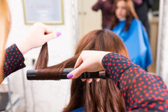 Stylist Using Flat Iron to Style Clients Hair Royalty Free Stock Photography