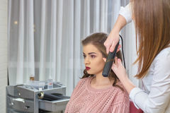 Stylist using hair straightener. Hairdresser working with customer Royalty Free Stock Photography