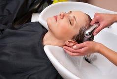 Stylist washing woman hair Royalty Free Stock Image