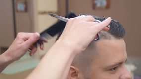 Stylist at work in barbershop, close shot. Hair cutting process. Master cutting hair with scissor and comb, recorded in. Hairdressing saloon. Selective soft stock footage