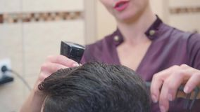 Stylist at work in barbershop, close shot. Master making modern hairdo with hair spray and comb. Recorded in. Hairdressing saloon. Selective soft focus. Blurred stock video footage
