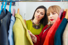 Stylist working with wardrobe. Girl with stylist choosing her fashion outfit. Women looking at clothes hanging deciding what to wear. Analysis of wardrobe Royalty Free Stock Images