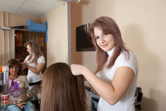 Stylist works on woman hair Royalty Free Stock Photo