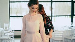 The stylist zips up the dress on a beautiful young model. stock footage