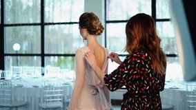 The stylist zips up the dress on a beautiful young model. stock video footage