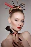 Styliste de modèle de jeune fille de beauté avec des brosses dans la coiffure de volume Images libres de droits