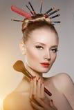 Styliste de modèle de jeune fille de beauté avec des brosses dans la coiffure de volume Photo libre de droits