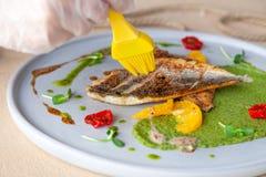 Styliste de nourriture avec le gland préparant pour tirer le filet frit de bar de mer avec la purée de pois, tomate, tranches ora photographie stock