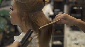 Styliste en coiffure à l'aide du fer et du peigne de cheveux pour le hairstyling de femme dans le studio de beauté Coiffeur créan clips vidéos