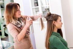 Styliste en coiffure appliquant la laque à de longs cheveux photographie stock