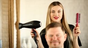 Styliste en coiffure blond utilisant le dessiccateur et le peigne pour l'homme photographie stock
