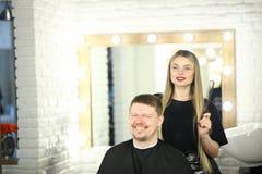 Styliste en coiffure de fille et client d'homme dans le studio de beauté photo stock