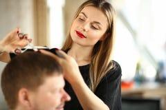 Styliste en coiffure de jeune femme coupant les cheveux masculins de client photographie stock