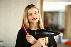 Styliste en coiffure de sourire avec Hairdryer et peigne rond photographie stock libre de droits