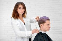 Styliste en coiffure féminin faisant la coupe de cheveux pour le jeune client avec les cheveux modifiés la tonalité photo libre de droits