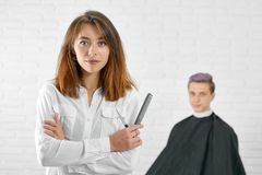 Styliste en coiffure féminin se tenant devant le jeune client avec les cheveux modifiés la tonalité photo stock