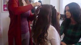 Styliste en coiffure faisant la coiffure tandis que composez l'artiste appliquant le mouvement lent de fards à paupières banque de vidéos