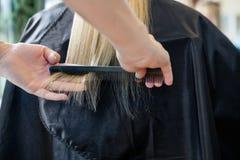 Styliste en coiffure peignant des cheveux de client images stock