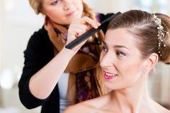 Styliste goupillant vers le haut de la coiffure d'une mariée photo libre de droits