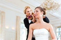 Styliste goupillant vers le haut de la coiffure d'une mariée photos stock