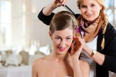 Styliste goupillant vers le haut de la coiffure d'une mariée images libres de droits