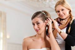 Styliste goupillant vers le haut de la coiffure d'une mariée images stock
