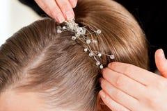 Styliste goupillant vers le haut de la coiffure d'une mariée image libre de droits