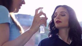 Styliste professionnel employant le jet pour le maquillage de difficultés sur le visage de la femelle dans le salon de beauté banque de vidéos