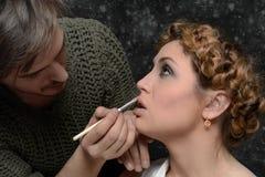 Stylisten applicerar makeup till en modell Arkivbilder