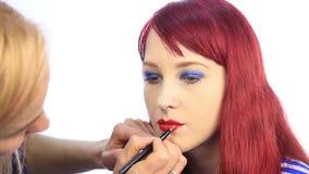 stylisten drar konturen av kanterna för modell` s med en röd blyertspenna sminkkonstnär att applicera läppstift med borsten på en
